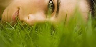 Девушка с зелеными глазами лежит на траве